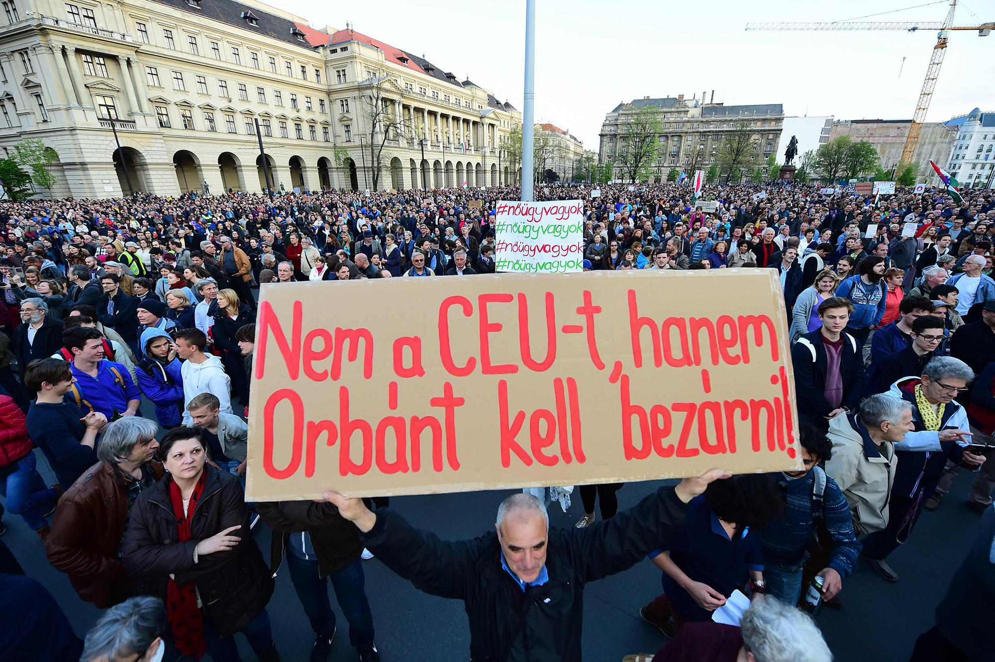 """Meeleavaldaja hoiab käes silti """"Ärge sulgege Kesk-Euroopa Ülikooli, Viktor Orbán vangi"""". Foto: Attila Kisbenedek"""