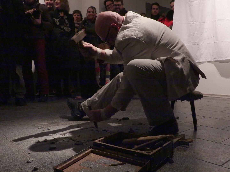 Jüri Ojaver püüdis performance'i käigus eemaldada graniidist põrandaplaati, et see sümboolsena seinale tõsta, kuid plaat osutas vastupanu. Need graniitplaadid oli Jüri Ojaver koos teiste skulptorite, Samba galerii asutajatega, kakskümmend viis aastat tagasi ise paika pannud. Foto: Epp Kubu