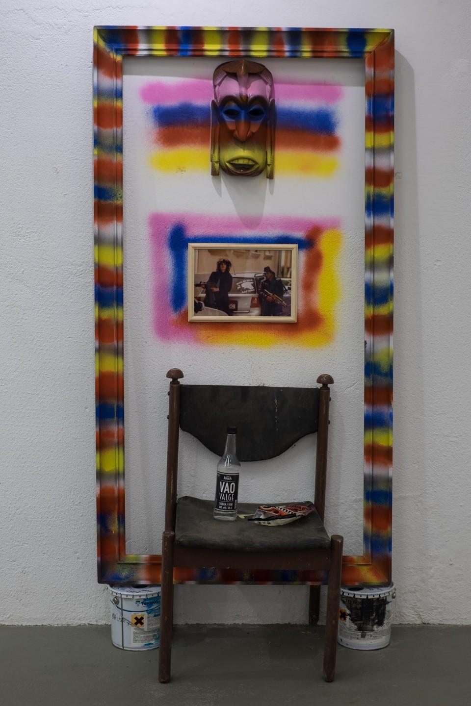 """Vao Valge pudeli kõrval vedeleb toolil Tõmmu kommide pakk. Fotol hoiavad Lekko ja Hammond käes mängupüsse ning poseerivad """"Siin ei ole Aafrika"""" autokleebisega. Teos näituselt """"Alone Together"""". Foto: Janis Kokk"""
