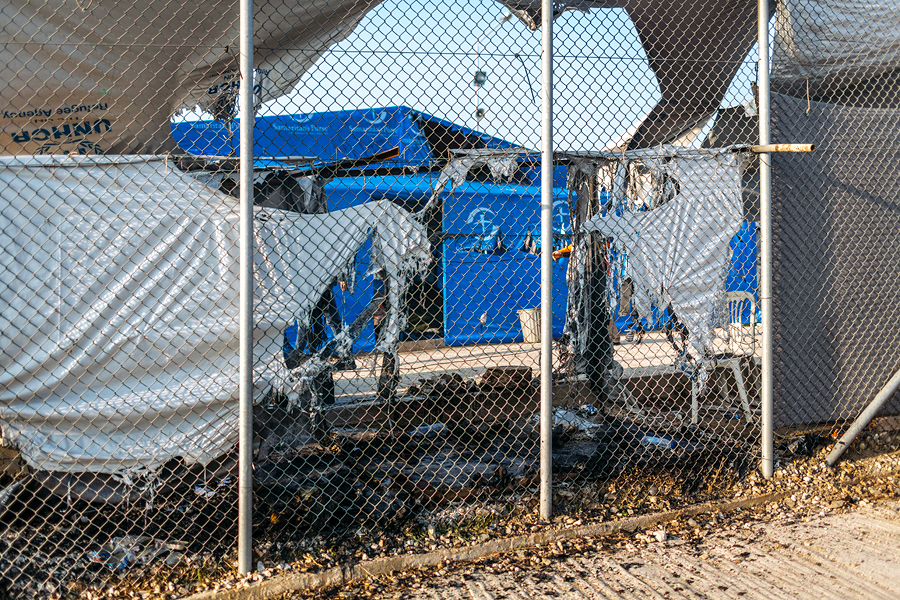 Moria põgenikelaagris puhkenud põleng on sulatanud laagri välisaeda katvasse kilesse ava, mis võimaldab heita sümboolse pilgu muidu suletud laagri sisemusse.