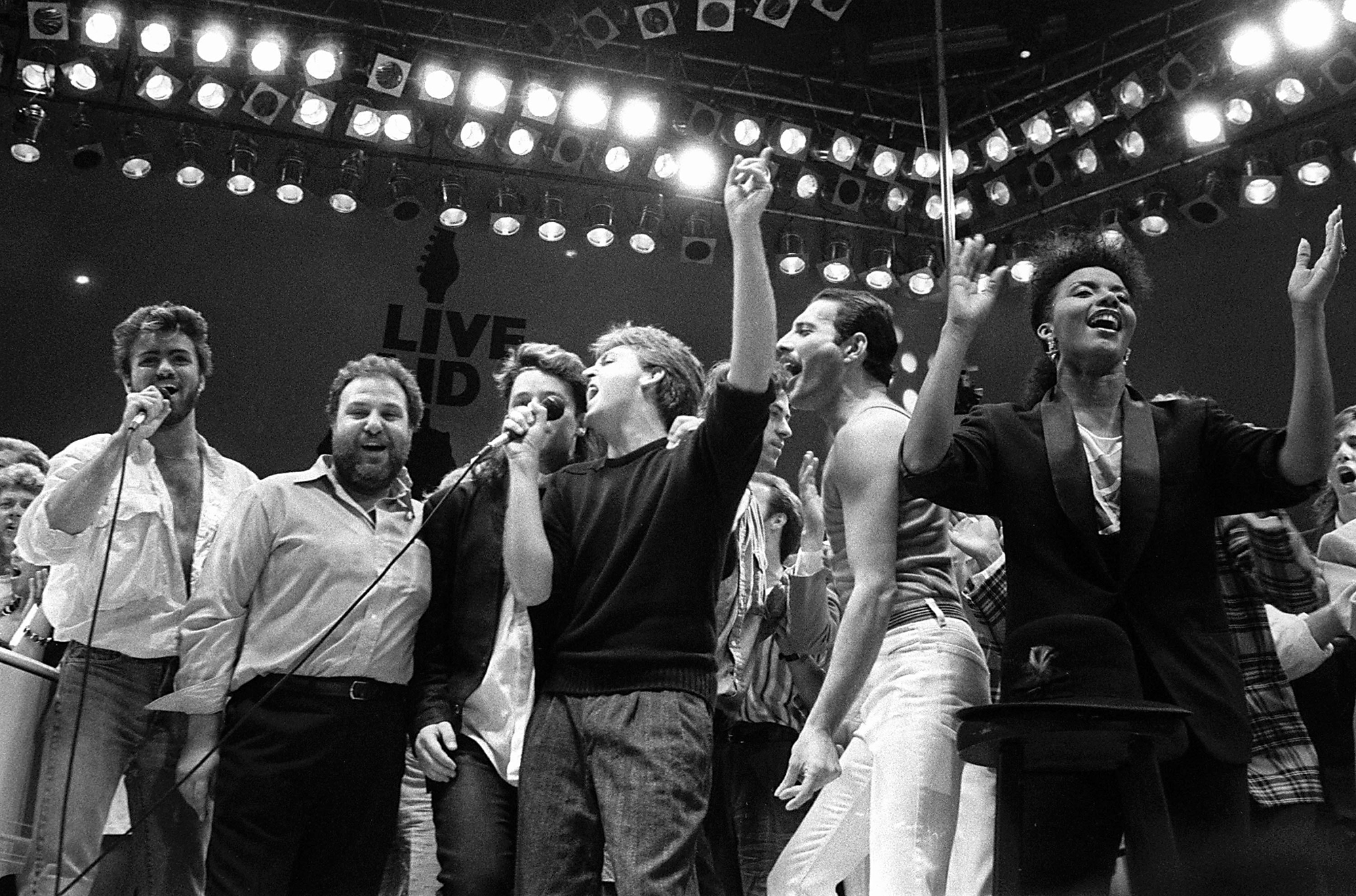 13. juuli 1985, George Michael, Harvey Goldsmith, Bono, Paul McCartney, Bob Geldof ja Freddie Mercury juubeldavad Live Aid kontserdil Londonis. Foto: Joe Schaber / AP Photo / Scanpix