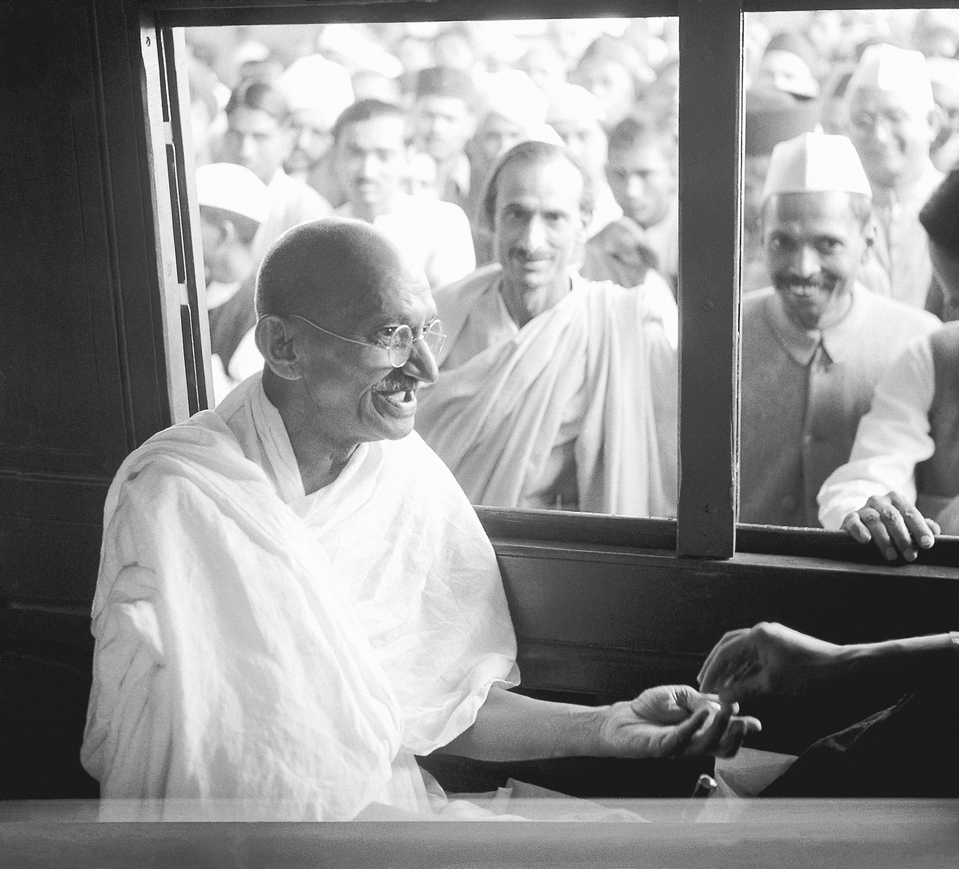 Mahatma Gandhi võtab rongis vastu annetuse. Allikas: Wikimedia Commons