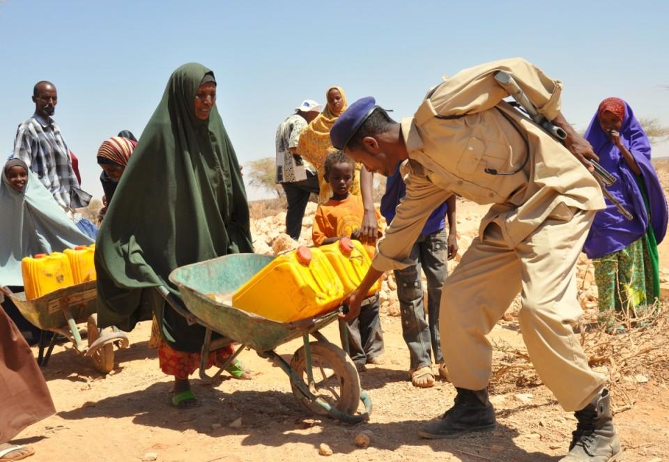 Alates 2011. aastast on Ida-Aafrikas sagenenud põuad, mis põhjustavad piirkonnas näljahäda. Selle tagajärjel on hukkunud üle 250 tuhande inimese ning miljonid on sunnitud kodudest lahkuma, et otsida eluks vajalikke tingimusi. Pildil aitab Somaalia politseinik naist käruga, millel on kanistrid humanitaarabi korras saabunud puhta joogiveega. Foto: Wikimedia Commonsi kasutaja Oxfam East Africa (CC BY 2.0)
