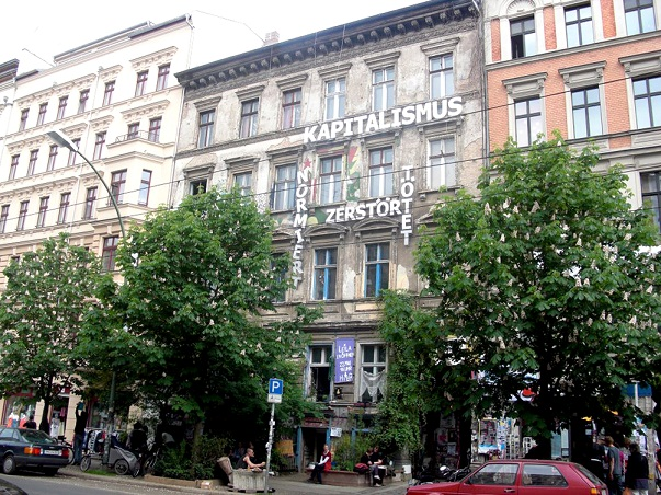 A building in Prenzlauer Berg that is surrounded by renovated buildings. It has been left like this most likely because it hasn't been possible to find it's lawful owner or their beneficiaries. The writing on the building: Capitalism - standardizes, destroys and kills.