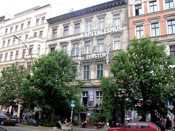 Renoveerimata hoone Prenzlauer Bergis, mis on ümbritsetud renoveeritud hoonetest. Hoone on renoveerimata tõenäoliselt seetõttu, et ei ole suudetud leida selle enne-nõukogudeaegset seaduslikku omanikku või nende pärijaid. Kiri hoonel: Kapitalism – normeerib, hävitab, tapab.