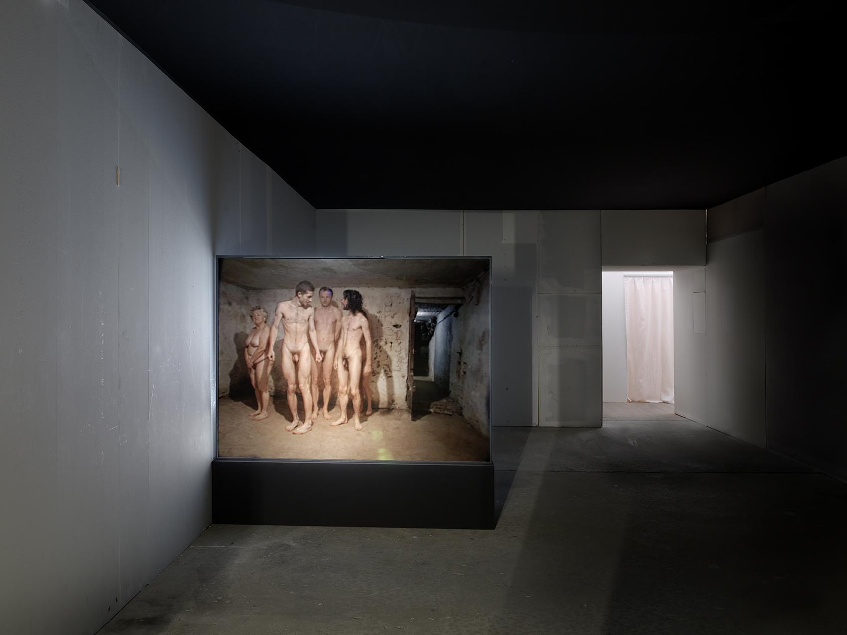 """Artur Żmijewski """"Kullimäng"""" (1999). Videoteos, kus grupp alasti inimesi mängib kunagi gaasikambrina kasutatud ruumis kulli. Foto: André Morin"""